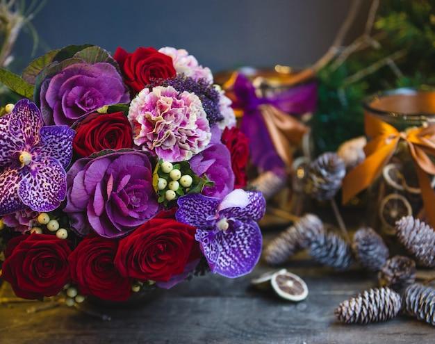 Um buquê de rosas vermelhas, flores cor de rosa e roxas com folhas na mesa de natal Foto gratuita