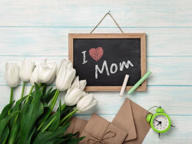 Um buquê de tulipas brancas com placa de giz e envelopes em placas de madeira azuis. dia das mães Foto Premium