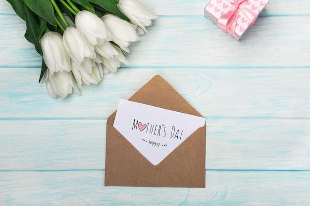 Um buquê de tulipas brancas com uma caixa de presente, nota de amor e envelope em tábuas de madeira azuis. dia das mães Foto Premium