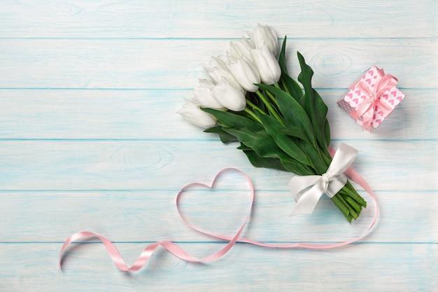 Um buquê de tulipas brancas e uma fita rosa sob a forma de um coração com uma caixa de presente em placas de madeira azuis. Foto Premium
