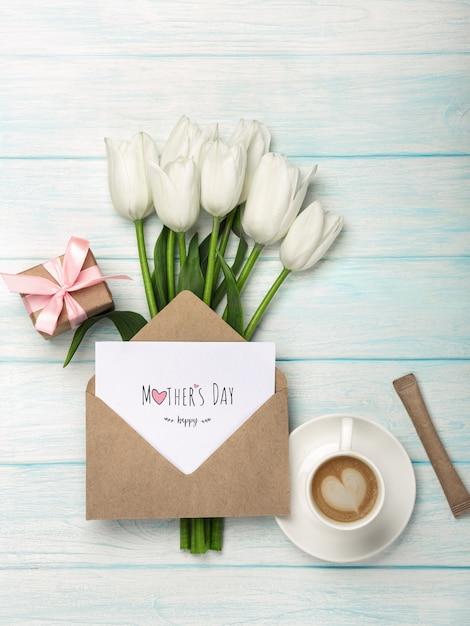 Um buquê de tulipas brancas, xícara de café, caixa de presente com uma nota de amor e envelope em tábuas de madeira azuis. dia das mães Foto Premium