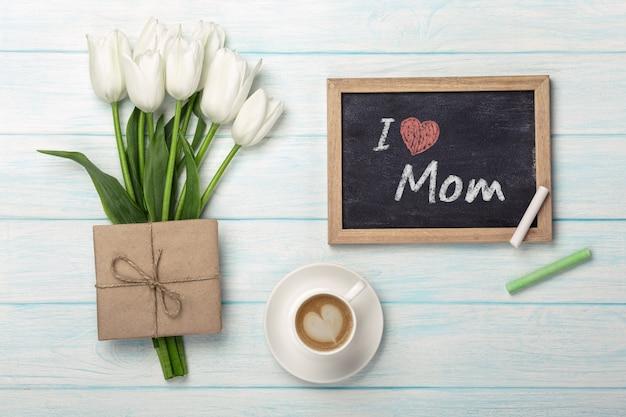 Um buquê de tulipas brancas, xícara de café com placa de giz e envelope em tábuas de madeira azuis. dia das mães Foto Premium