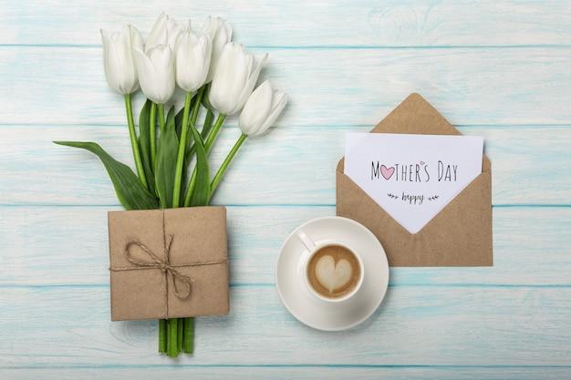 Um buquê de tulipas brancas, xícara de café com uma nota de amor e envelope em tábuas de madeira azuis. dia das mães Foto Premium