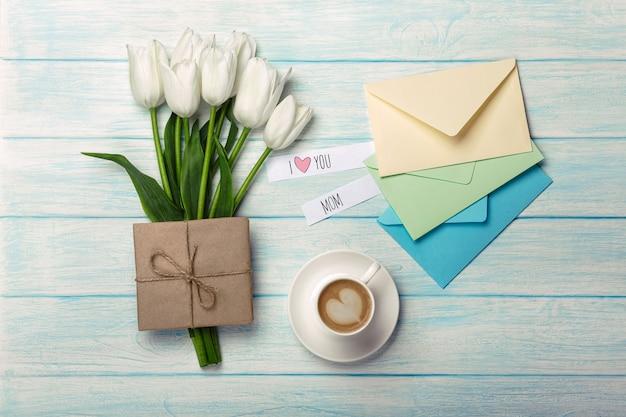Um buquê de tulipas brancas, xícara de café com uma nota de amor e envelopes de cor em placas de madeira azuis. dia das mães Foto Premium