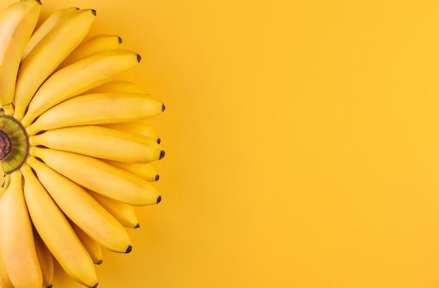 Um cacho de bananas maduras pequenas em um espaço de cópia de fundo amarelo Foto Premium