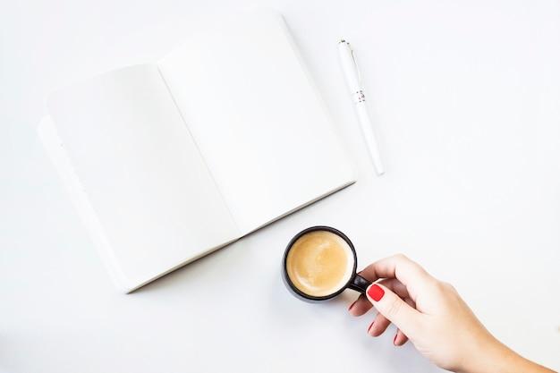 Um caderno aberto com lençóis brancos limpos ao lado de uma caneta branca e uma xícara de café Foto Premium