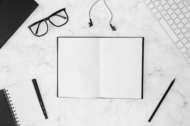 Um caderno em branco aberto com óculos; diário; lápis; fone de ouvido; teclado na mesa branca Foto gratuita
