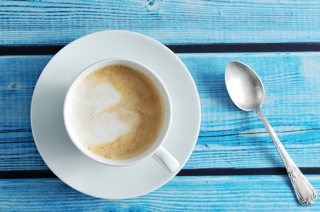 Um café espumoso com cappuccino em uma caneca branca sobre um fundo azul de madeira Foto Premium
