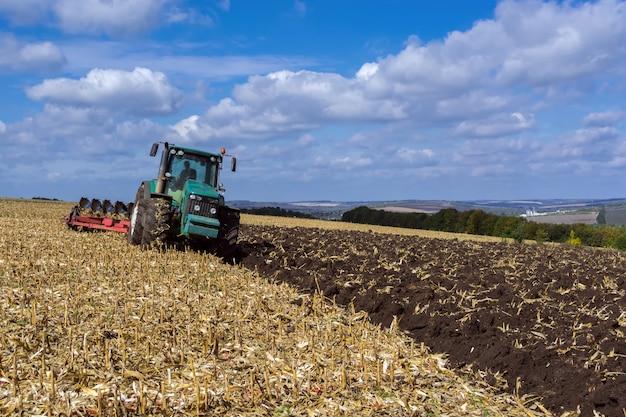 Um campo arado após a colheita de milho com um trator completo com um arado de oito corpos Foto Premium