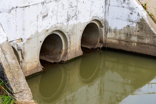 Um cano de esgoto ou esgoto ou esgoto descarrega água residual em um rio. Foto Premium