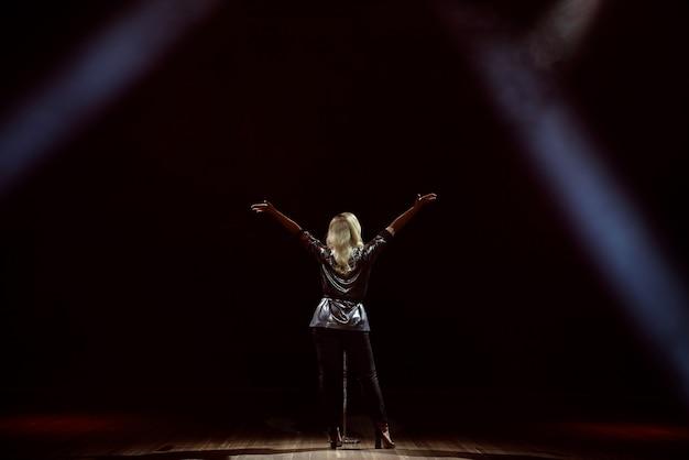 Um cantor da jovem mulher no estágio durante uma opinião do concerto da parte traseira. Foto Premium