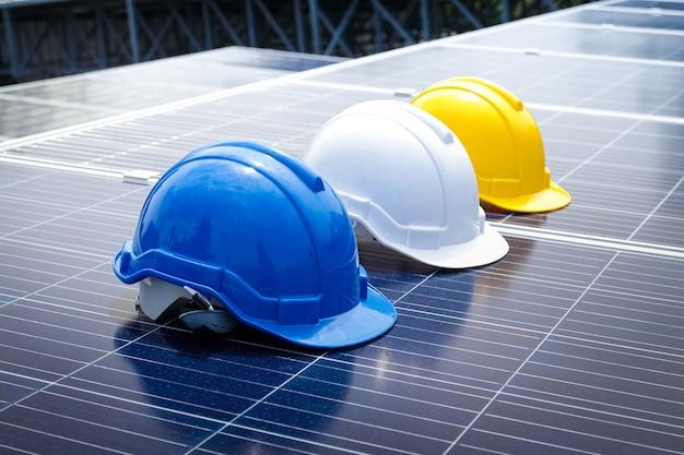 Um capacete de segurança para evitar batidas de cabeça durante o trabalho, um mecânico azul, branco e amarelo é colocado no painel solar. conceito de tecnologia de energia, trabalho. copie o espaço Foto Premium