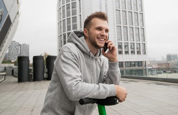 Um cara atraente com barba conta ao amigo ao telefone sobre a conveniência de alugar um veículo elétrico. conceito de transporte ecológico. roupas casuais. blocos de apartamentos em segundo plano. Foto Premium