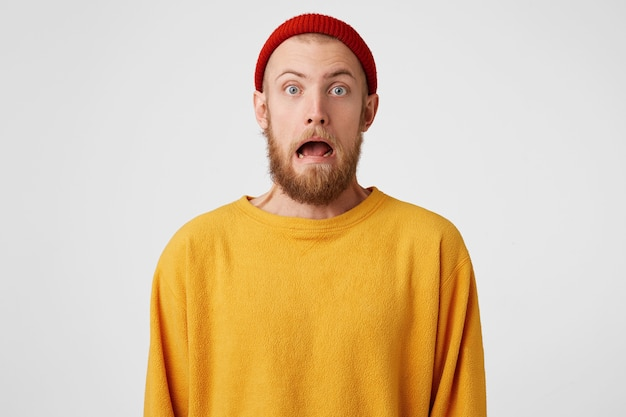 Um cara barbudo assustado com olhos azuis me encara com uma careta de horror Foto gratuita