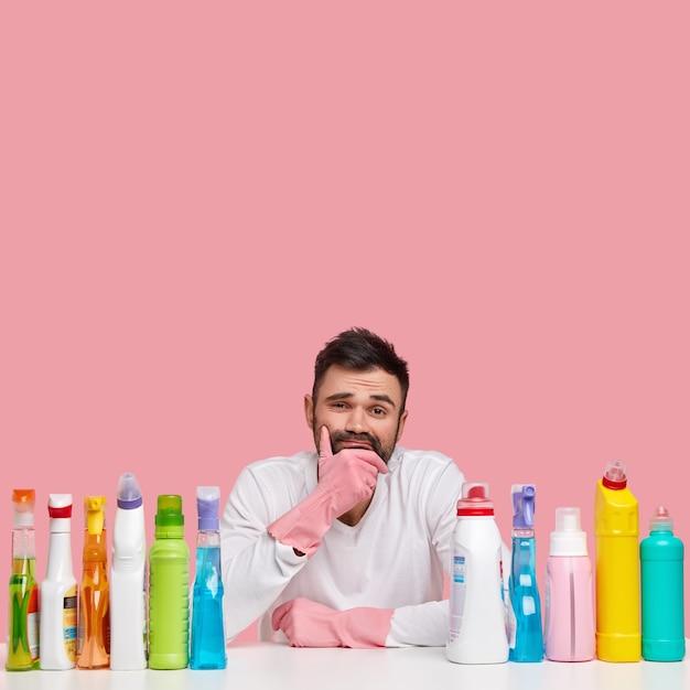 Um cara com a barba por fazer cansado segura o queixo, vestido com roupas casuais, senta-se à mesa com detergentes químicos de limpeza, lava tudo, posa sobre uma parede rosa com espaço livre, parece relutante Foto gratuita