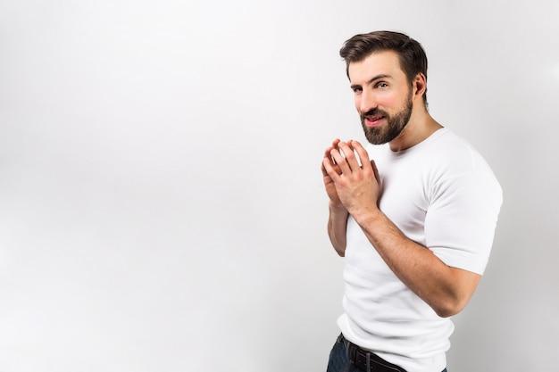 Um cara com uma visão astuta está colocando os dedos nas duas mãos. ele inventou alguma coisa e quer fazer isso o mais rápido possível. isolado na parede branca Foto Premium
