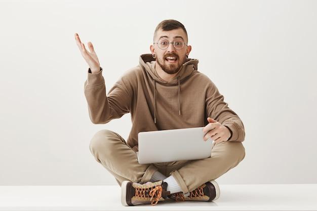 Um cara entusiasmado discute algo sentado de pernas cruzadas com um laptop Foto gratuita