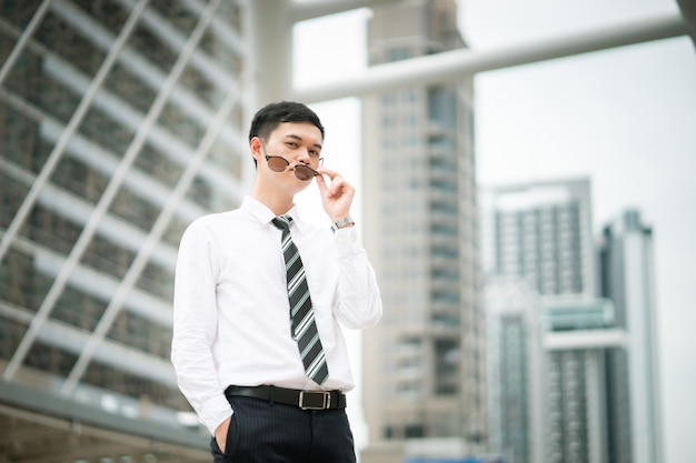 Um cara esperto está parado na cidade, ele está vestindo camisa branca e gravata. Foto Premium