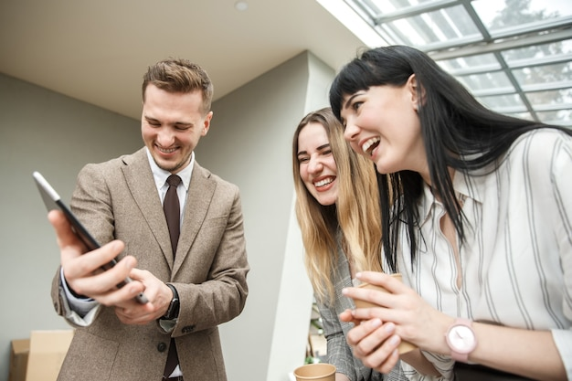 Um cara está mostrando algo em seu tablet para duas meninas Foto Premium