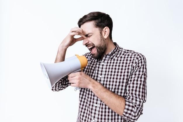 Um cara jovem grita em um megafone de dor. Foto Premium