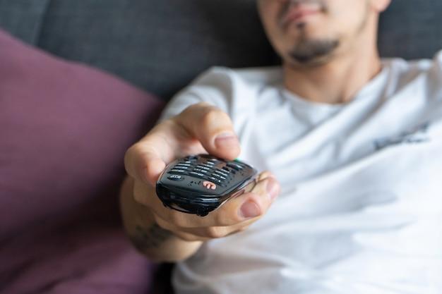 Um cara magro em roupas domésticas se senta em um sofá e assiste tv. Foto Premium
