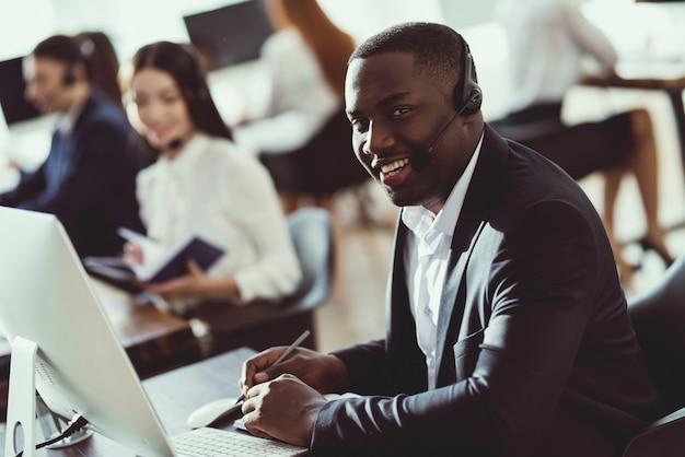 Um cara negro trabalha em um call center. Foto Premium