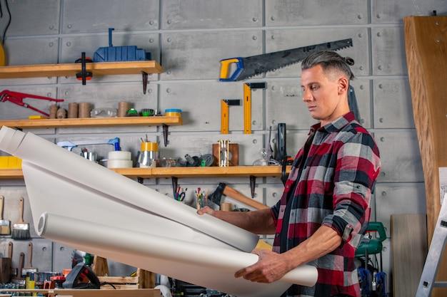 Um carpinteiro trabalha. carpinteiro, estudando o projeto de desenho. no contexto do workshop Foto Premium