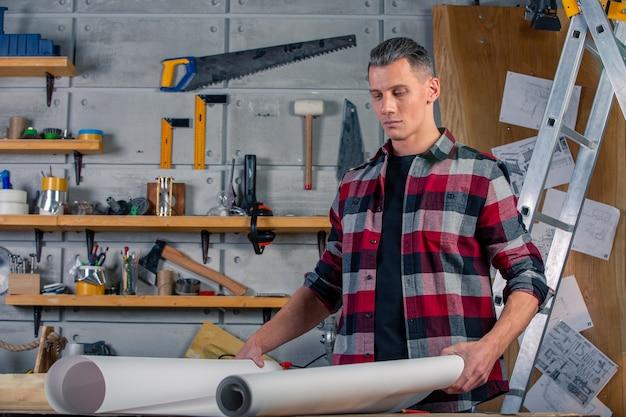 Um carpinteiro trabalha. carpinteiro estudando projeto de desenho. no contexto da oficina. Foto Premium