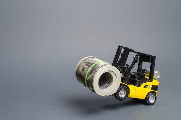Um carregador amarelo fica nas rodas traseiras segurando um grande pacote de dólares. conceito de investimento Foto Premium