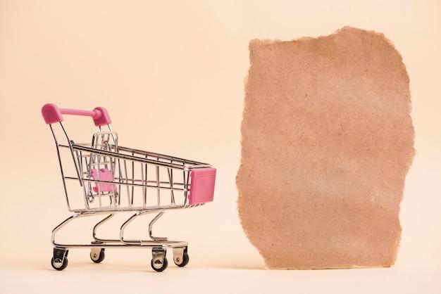 Um carrinho de compras em miniatura vazio perto do pedaço de papel rasgado contra o pano de fundo colorido Foto gratuita