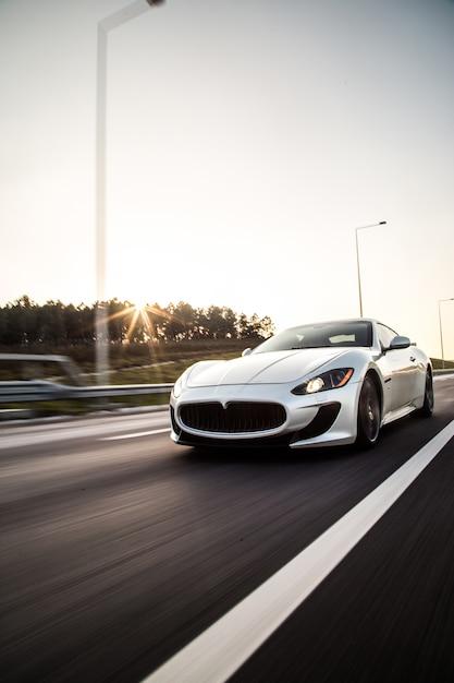 Um carro esporte de cor metálica tira com alta velocidade na estrada. Foto gratuita