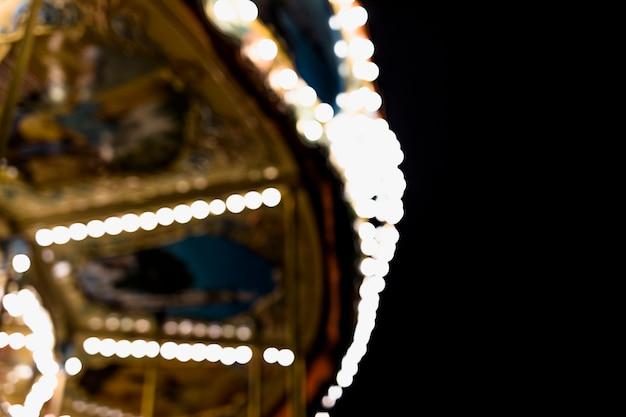 Um carrossel embaçado no parque de diversões contra o pano de fundo preto Foto gratuita