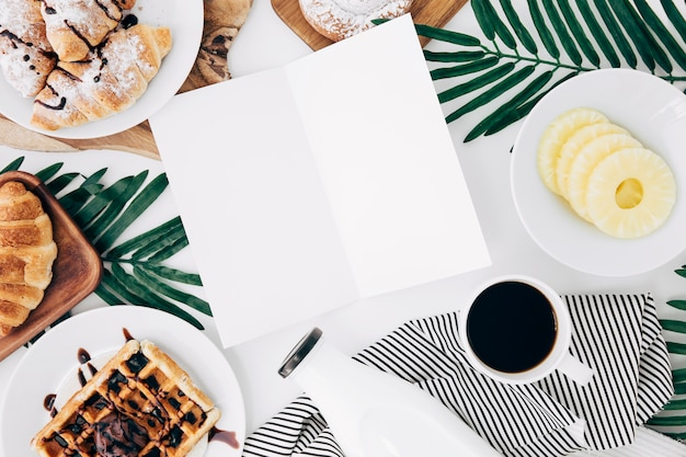 Um cartão em branco aberto cercado com café da manhã na mesa branca Foto gratuita