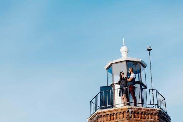 Um casal amoroso abraços no topo de um farol Foto Premium