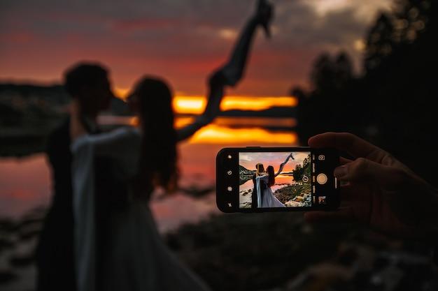 Um casal de noivos em pé ao lado de um rio. no fundo, a vila ao pôr do sol, atirando no telefone Foto Premium