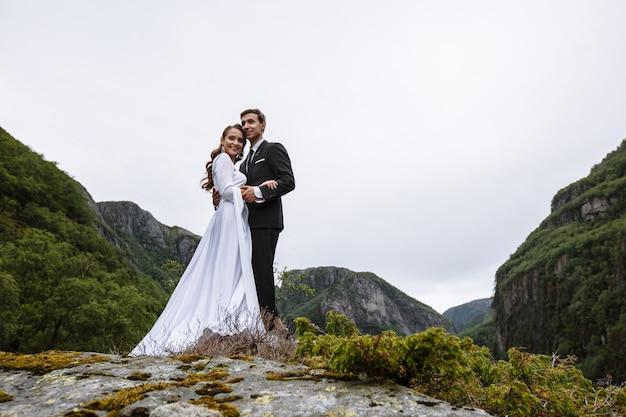 Um casal de noivos em pé sobre uma rocha coberta de musgo Foto Premium