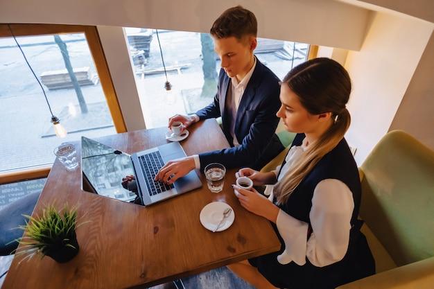 Um casal elegante bebe café da manhã no café e trabalha com um laptop Foto Premium