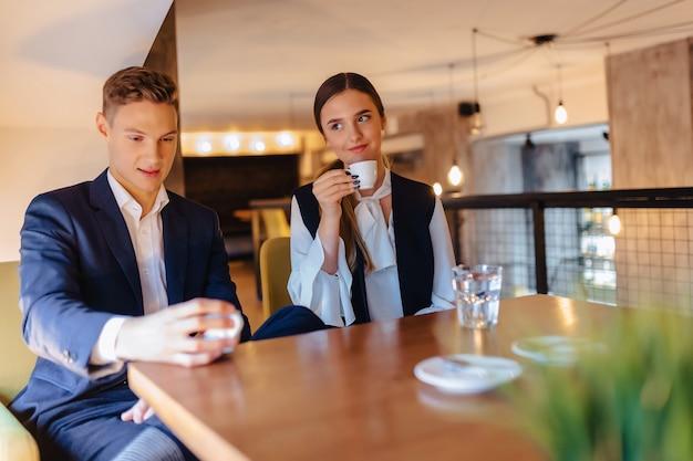 Um casal elegante bebe café da manhã no café, jovens empresários e freelancers Foto Premium
