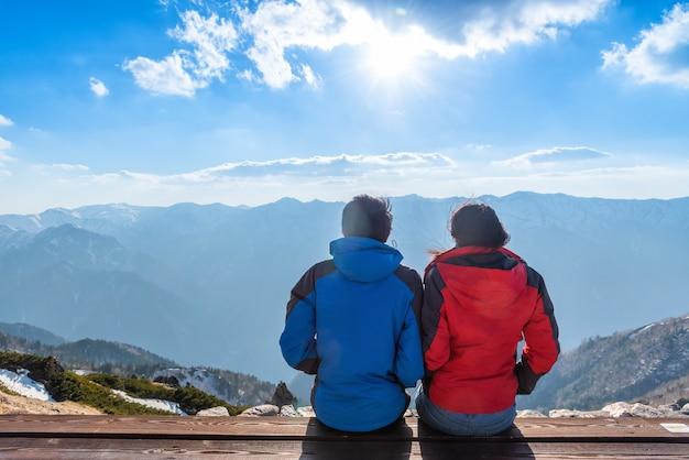 Um casal está vendo a paisagem do monte tsubakuro dake ao pôr do sol. cordilheira do parque chubu-sangaku dos alpes do norte de japão. Foto Premium