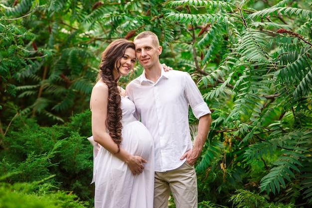 Um casal feliz grávida está andando na natureza. Foto Premium