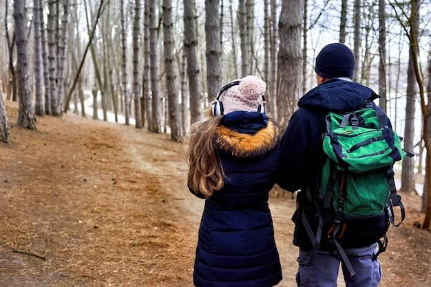 Um casal na floresta de fim de inverno com mochila Foto Premium