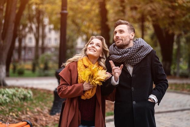 Um casal num encontro olhando para cima andando no parque outono de mãos dadas. foto ao ar livre de um jovem Foto Premium
