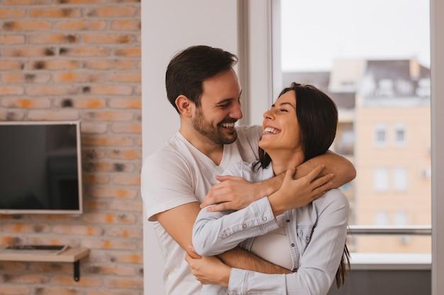 Um casal se divertindo muito perto da janela Foto Premium