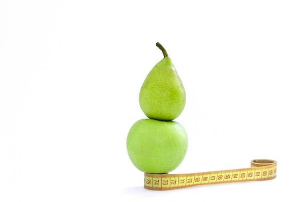 Um centímetro, uma maçã e uma pêra verde ficar em um fundo branco Foto Premium