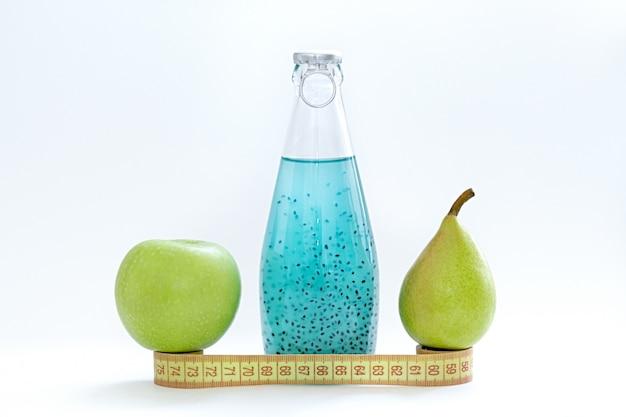 Um centímetro, uma maçã, uma pêra e garrafas de vidro com semente de manjericão azul ficar em um fundo branco Foto Premium