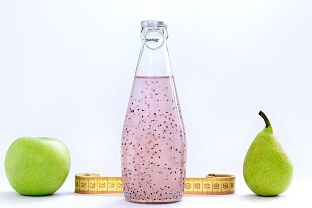 Um centímetro, uma maçã, uma pêra e garrafas de vidro com semente de manjericão rosa ficar em um fundo branco Foto Premium