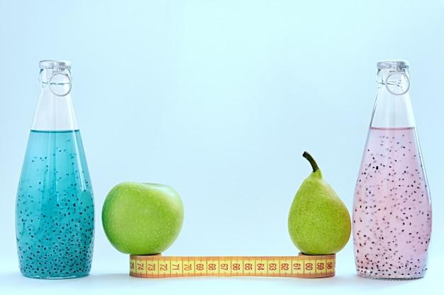 Um centímetro, uma maçã, uma pêra e garrafas de vidro com sementes de manjericão de cor rosa e azul ficar sobre um fundo azul Foto Premium