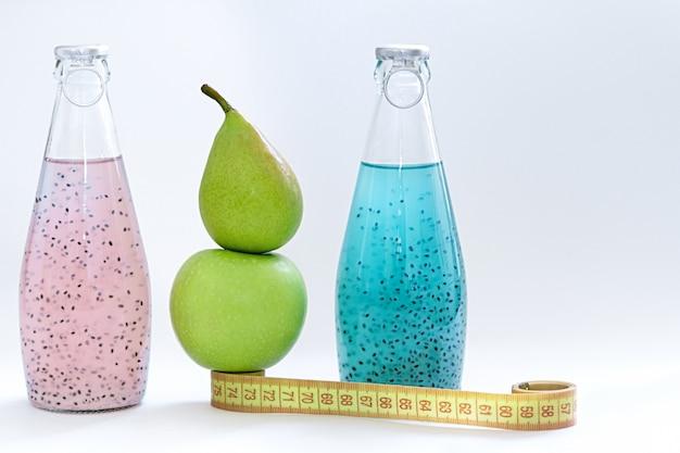 Um centímetro, uma maçã, uma pêra e garrafas de vidro com sementes de manjericão rosa e azul ficar em um fundo branco Foto Premium