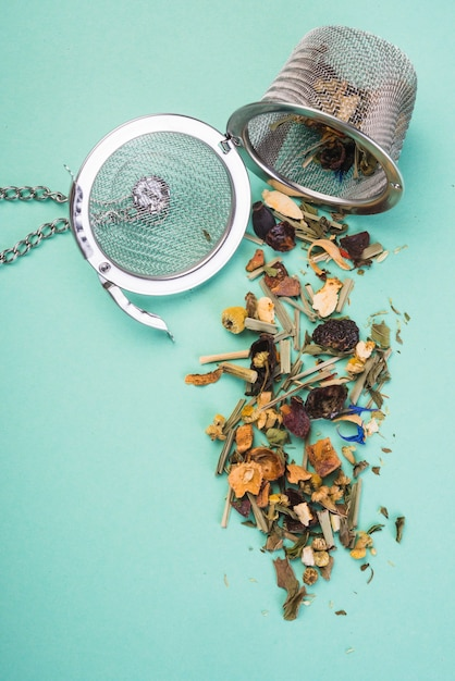 Um, chá, infundindo, cesta, com, um, abertos, chá, ervas, ligado, colorido, fundo Foto gratuita