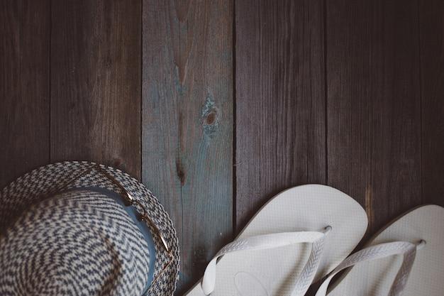 Um chapéu, óculos escuros e chinelos brancos sobre o fundo de madeira Foto Premium